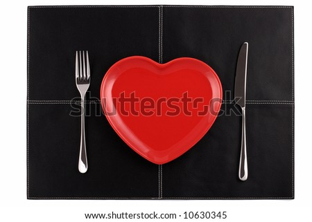 empty red heart plates with a knife and fork on a black leather place mat