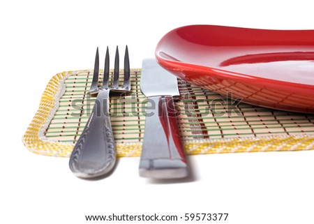 Empty red plate with knife and fork