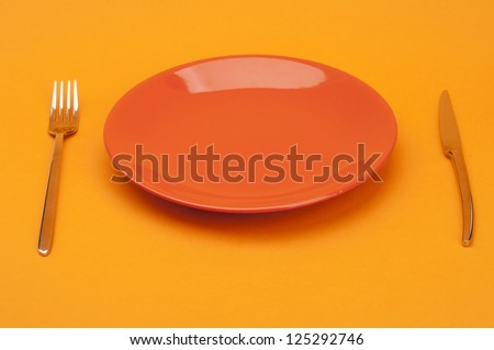 Empty red plates with fork and knife
