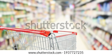 empty red shopping cart in supermarket aisle