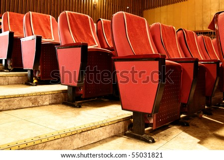 Empty red theater seats close up