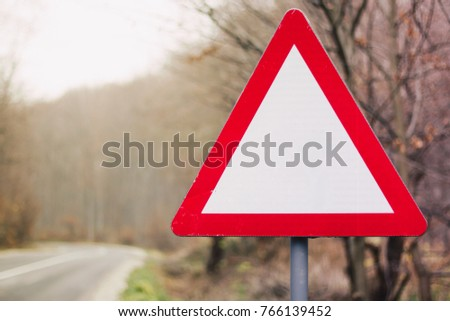 Empty red triangle road sign with nobody on the street and trees in the background #766139452