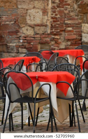 Empty restaurant chairs and tables in the old Italian street