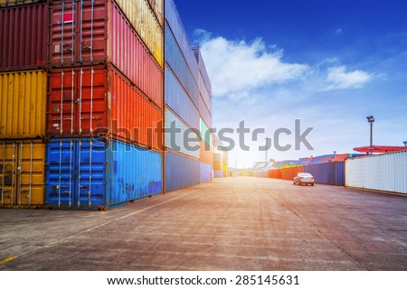 Empty road and containers in harbor at sunset
