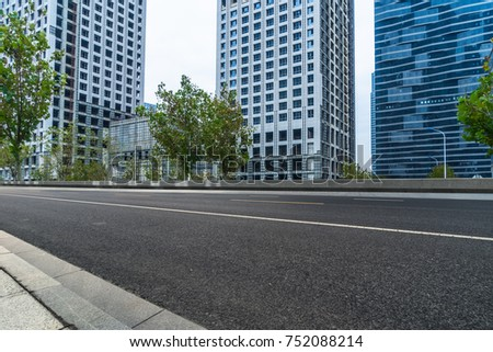 empty road and modern office block buildings against sky, china.