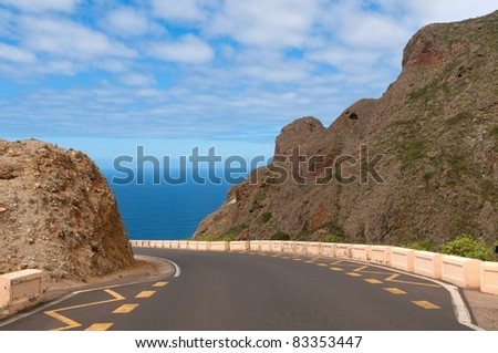 Empty road between mountains leading to the sea, Canary islands, Spain
