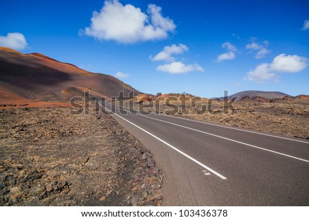 Empty road crossing the lava in the mountain, Lanzarote, Canary islands, Spain. Vertical view