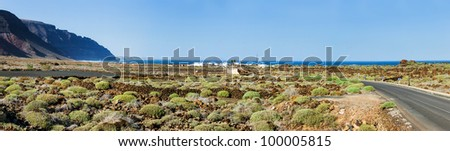 Empty road crossing the lava in the mountain, volcano backround. Panorama. Lanzarote, Canary islands, Spain