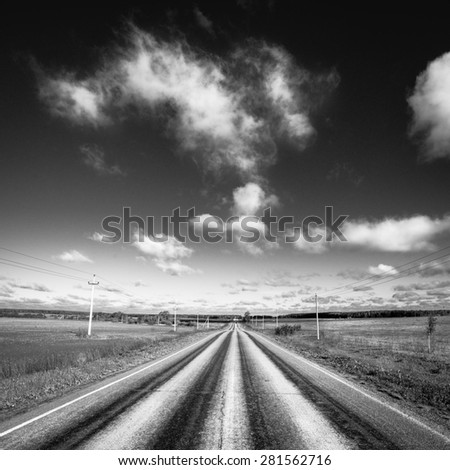 Empty road disappearing into the distance, sky with clouds. Black and white photography