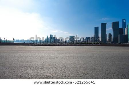 Empty road floor surface with modern city landmark buildings of Shanghai bund Skyline