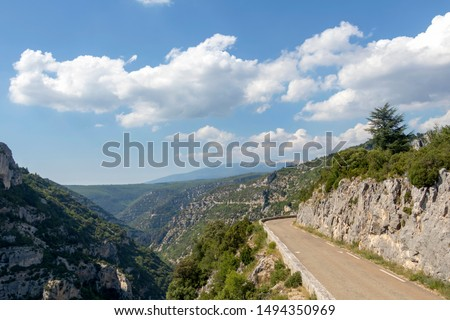 Empty road in the Gorge de la Nesque, view over a rocky and gray canyon with green trees and blue sky, a long valley created by the river La Nesque in the Vaucluse Mountain, Provence, France #1494350969