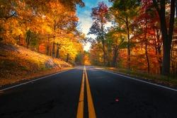 Empty road leading through fall foliage at Bear Mountain New York. During Peak Foliage season.