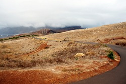 Empty road, terra ground, cloudy sky and windmills. Madeira, Portugal scenery. Eco and renewable energy sources trend