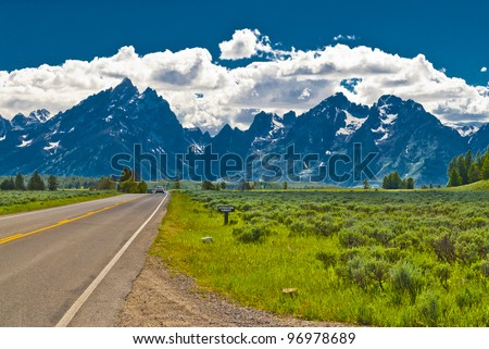 Empty road to Grand Teton Mountains with dramatic clouds in the background - stock photo