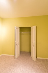Empty room in a modern house with the open closet, cabinet doors. Interior design.