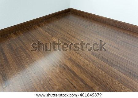 empty room interior, brown wood laminate floor and white mortar wall