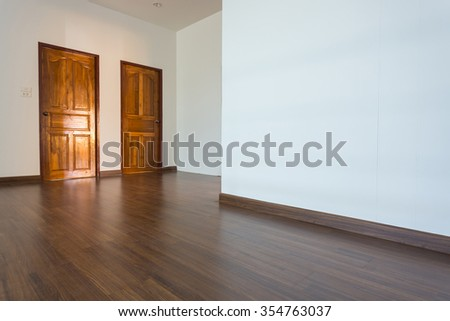 empty room, white mortar wall background and wood laminate floor in residential