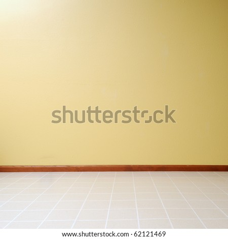 Empty room with a linoleum floor with a yellow painted wall - stock photo