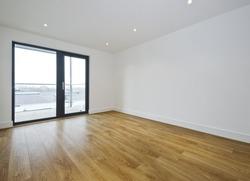 empty room with balcony access and hard wood floor
