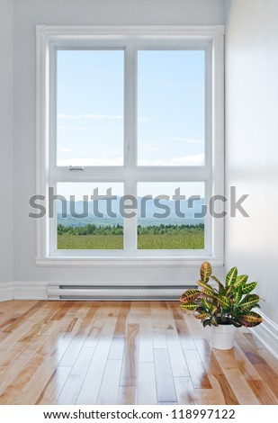 Empty room with beautiful view over field and mountains.
