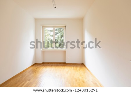 Empty room with parquet. Bright window with a view of nature. Nobody inside