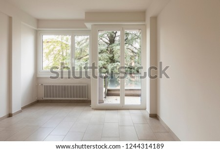Empty room with radiators and large windows overlooking nature. Front view