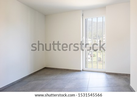Empty room with white walls and bright window. Nobody inside
