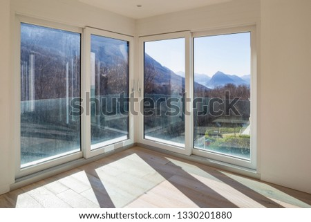 Empty room with white walls and windows overlooking the mountains. Nobody inside