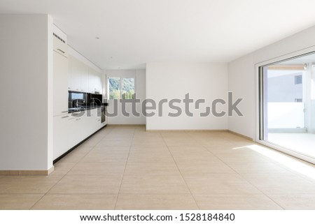 Empty room with white walls, travertine floor and white kitchen and black marble. Copy space. Nobody inside