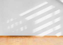 Empty room with wooden floor and diagonal shadows on white wall