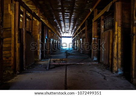 Empty rotting horse stalls in an abandoned barn with open barn doors letting in light at the end of the room #1072499351