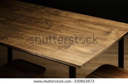 Empty rough wooden table top in the dark room