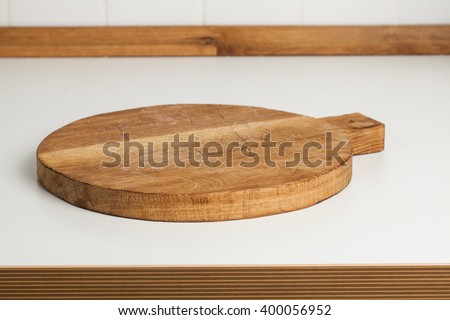 Empty round cutting board on a white kitchen top.