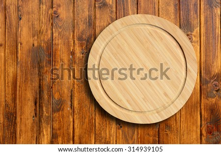 Empty round cutting board on a wooden table.Top view