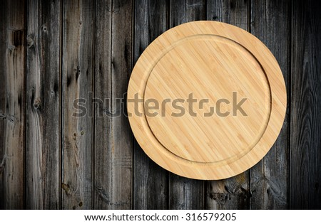 Empty round cutting board on a wooden table.Top view,rustic style