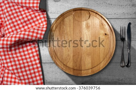 Empty round cutting board on a wooden table with silver cutlery, fork and knife, and a red and white checkered tablecloth