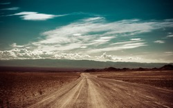 Empty rural road going through prairie under cloudy sky in Charyn canyon. State National Paleontology Park in Kazakhstan. Vintage style processing image