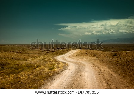 Empty rural road going through prairie under cloudy sky in Charyn canyon. State National Paleontology Park in Kazakhstan. Vintage style processing image #147989855