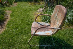 Empty rusted metal chair, metaphor for grief, loss, and death, green grass path, horizontal aspect