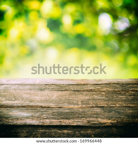 Empty Rustic Wooden Board Or Old Weathered Garden Table Top With Summer Greenery And Golden Sunlight In The Background