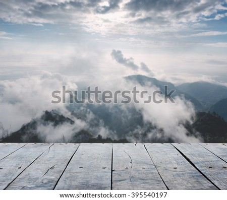 empty rustic wooden table and mountain with mist morning blurred background, for product display