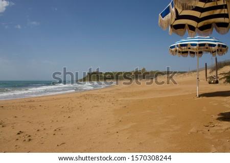 Empty sandy beach with umbrellas, Marinella, near Agrigento, Sicily, Italy