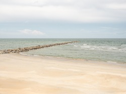 empty sandy tropical beach. wide beach on island. copy space provided. wave breaker on shore.