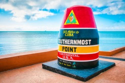 Empty scenic view of the colorful concrete buoy featuring the municipal seal of Key West marking the southernmost point of the continental USA in Florida