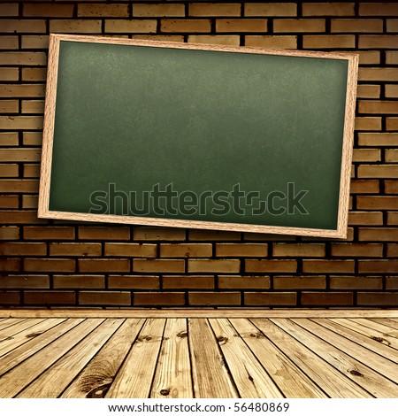 Empty school blackboard at brick wall in interior with wooden floor