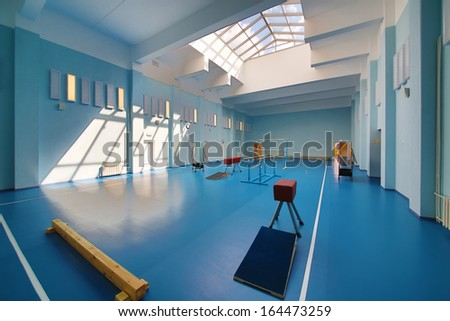 Empty school gymnasium with blue floor and exercise equipment.