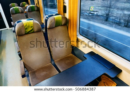 Empty seats in train compartment with large windows.  #506884387
