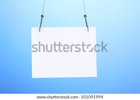 Empty sheet of a paper on fish hooks on blue background