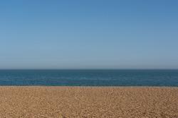 Empty shingle beach with clear blue sky and sea. Aldeburgh Beach, Aldeburgh, Suffolk. UK