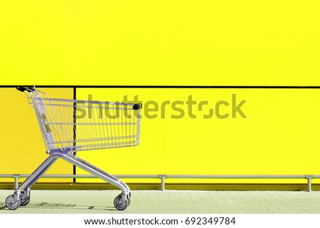 Empty Shopping Cart for buyer, parked in front of large supermarket. Consumerism concept #692349784
